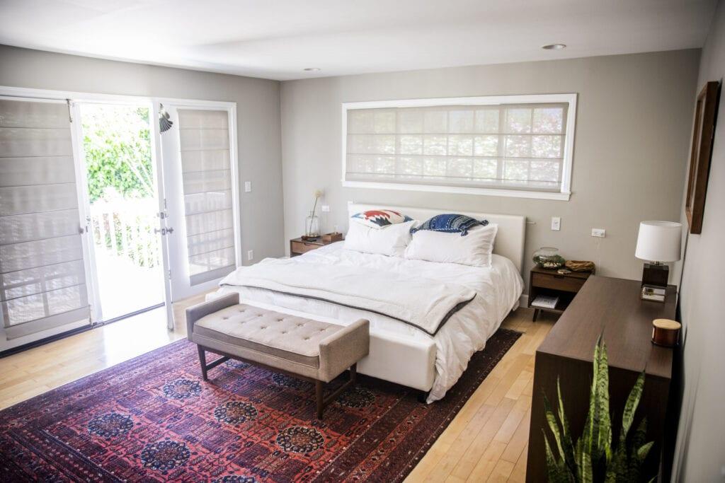 A master bedroom with a balcony door open