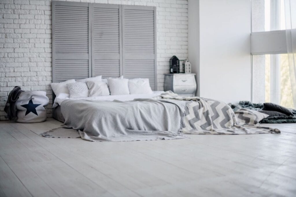 Gray and white bedroom with creative headboard