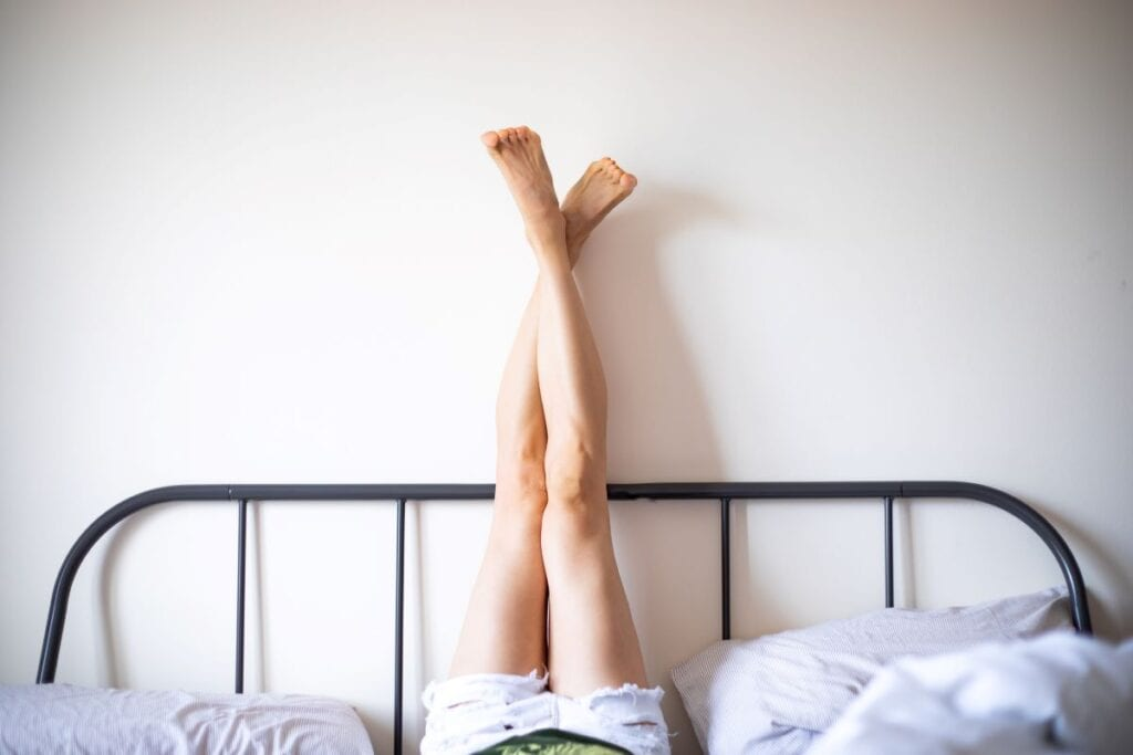Woman with legs kicked up against wall and metal headboard