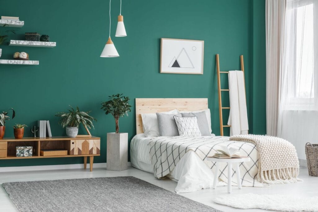 Modern bedroom with green walls and bed with wood headboard