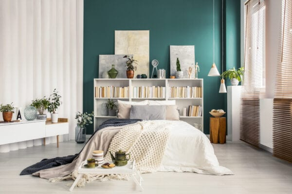 Bedroom with green accent wall, book shelf is being used as headboard