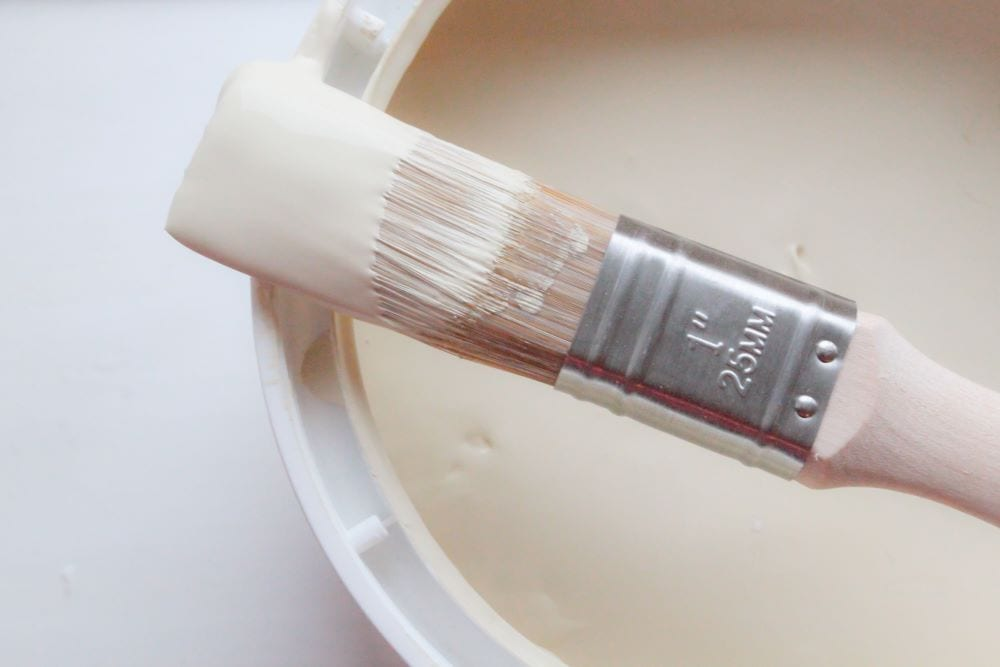 Close up of cream paint can and paintbrush