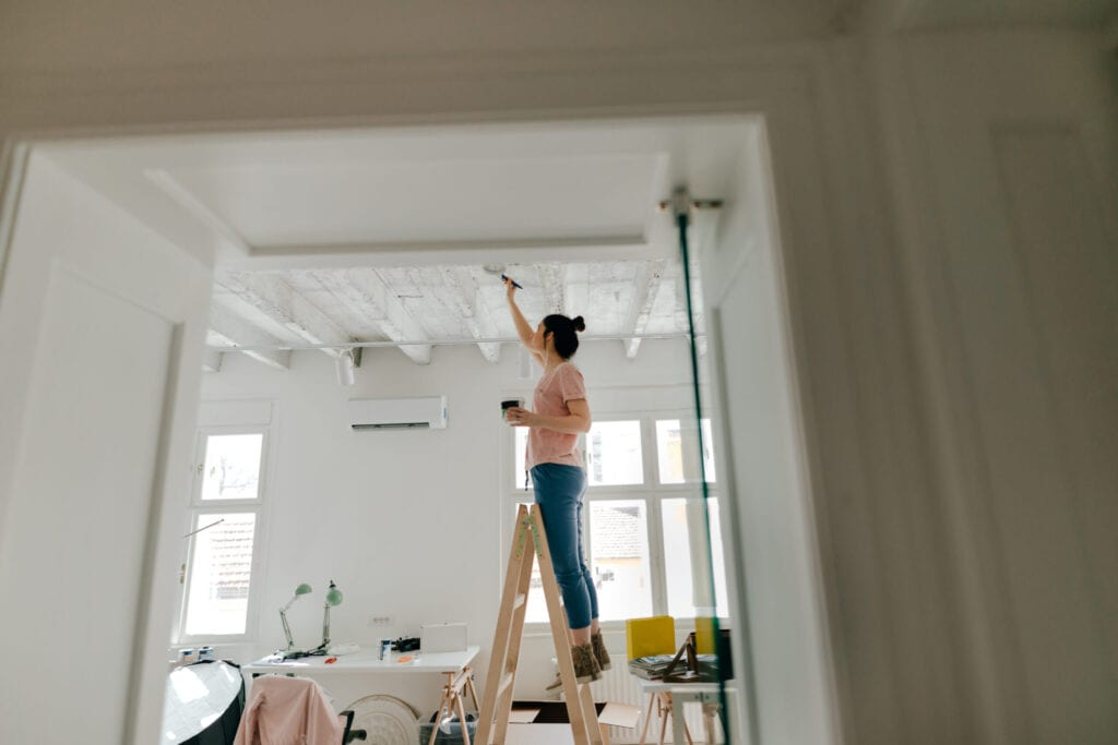Young woman painting interior of apartment