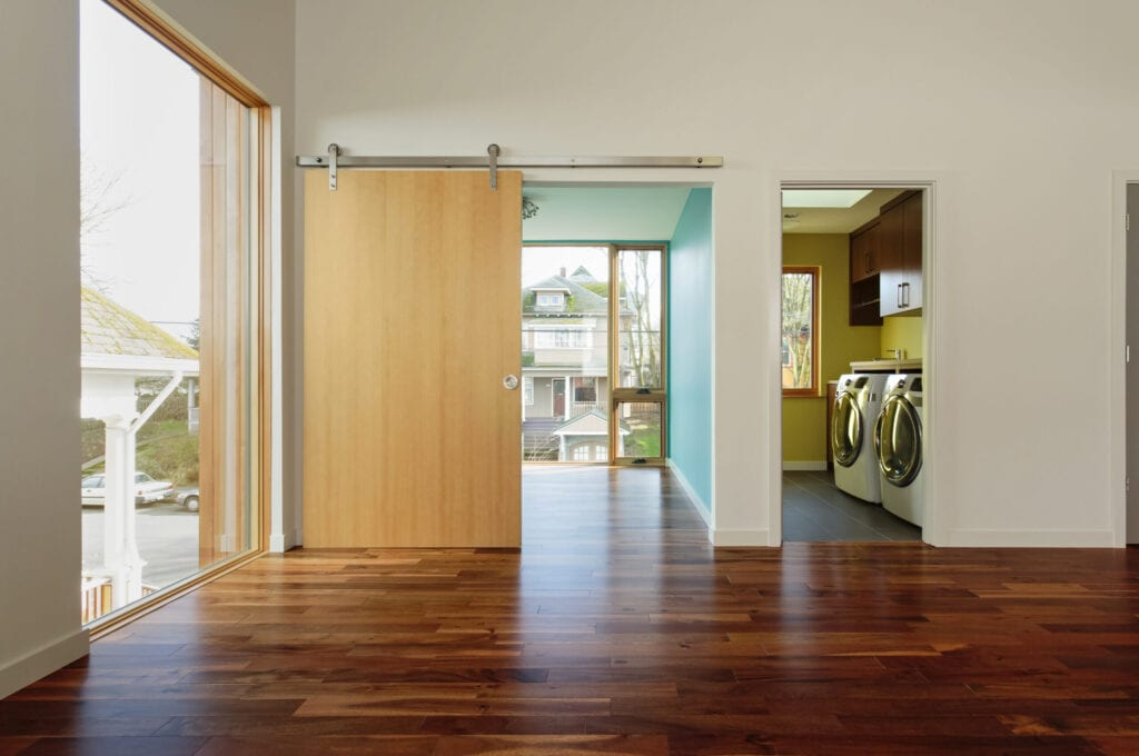 Modern home interior with View of upstairs laundry room and hardwood floors and barndoor style door.
