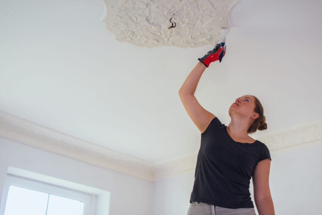 Woman repainting stucco in a house.