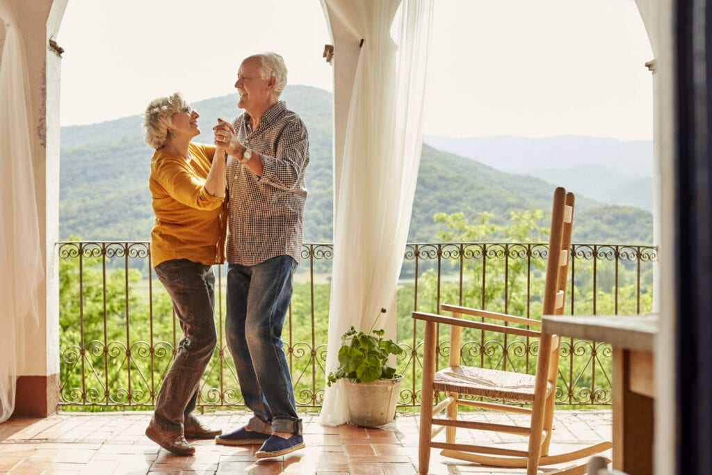 Loving senior couple dancing in balcony. Happy man and woman are spending leisure time together. They are at home.