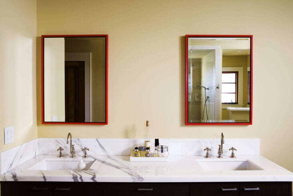 bathroom with red outlined mirrors