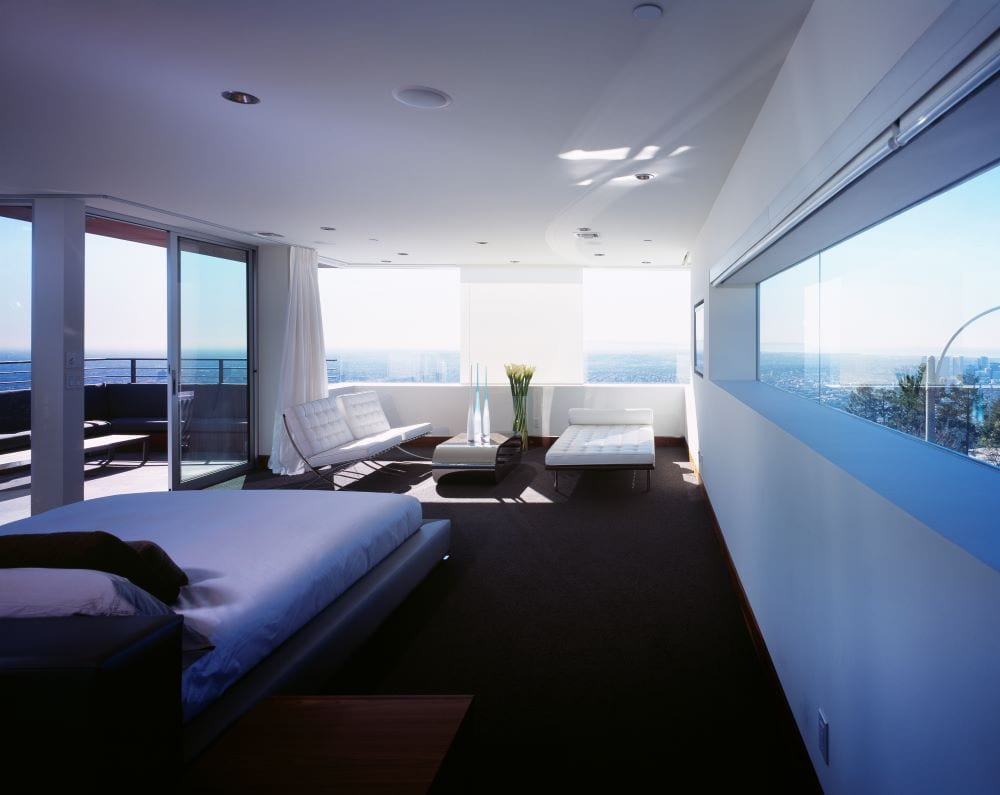 Dabyed and lounge chairs in bedroom overlooking city