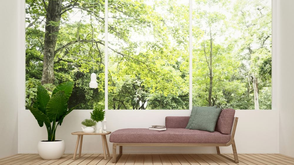 Pink daybed in front of large windows