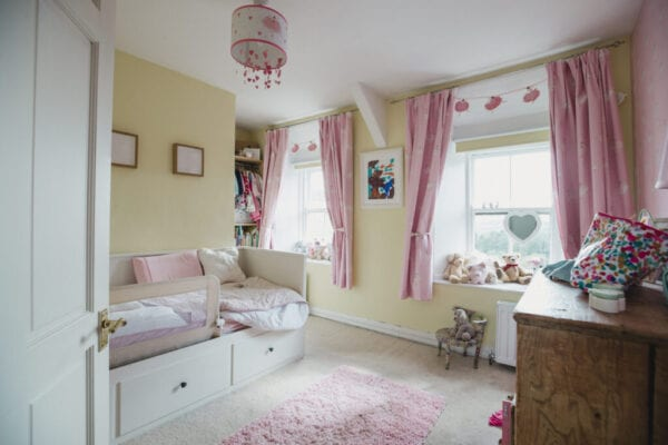 Feminine childhood bedroom with pink furnishings.
