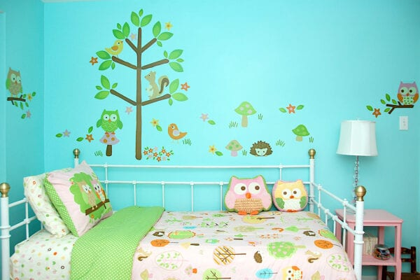 Girl bedroom painted bright turquoise and decorated with mushrooms and woodland.