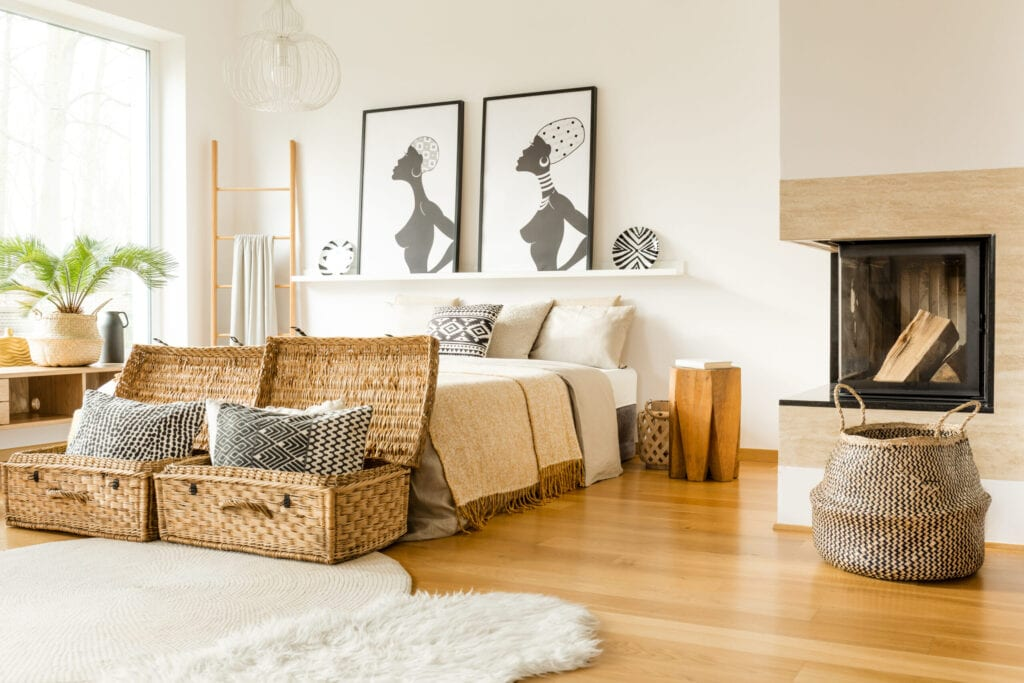 Fireplace, wattle boxes with pillows, bed, African posters in a boho bedroom interior
