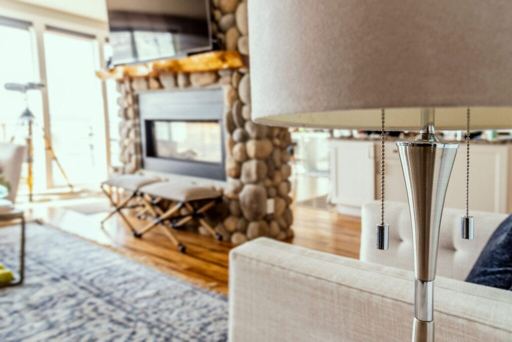 Close up photo of floor lamp, fireplace and tv in background