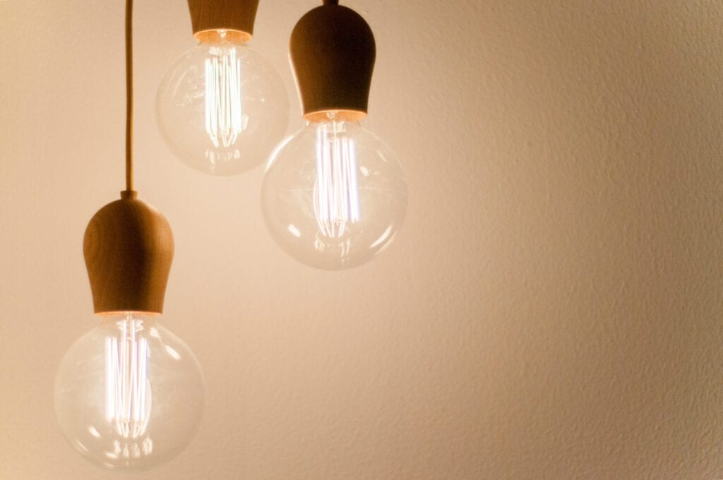 Three lit-up lightbulbs hanging by cords on a beige background.