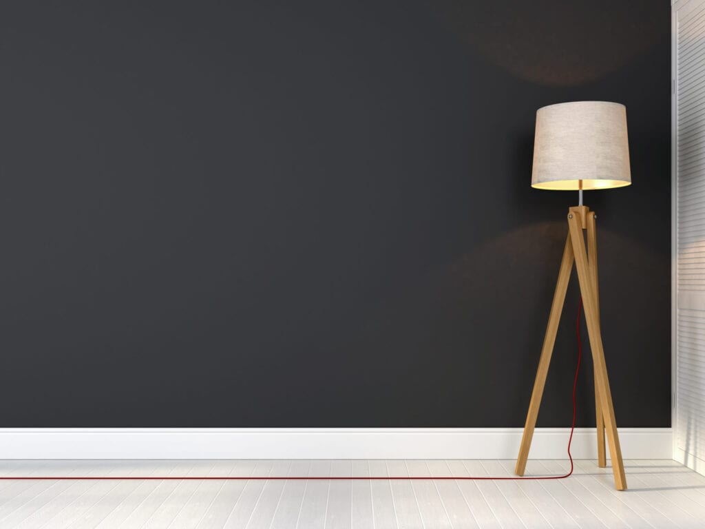 Stylish tripod lamp with red wire on a background of gray wall
