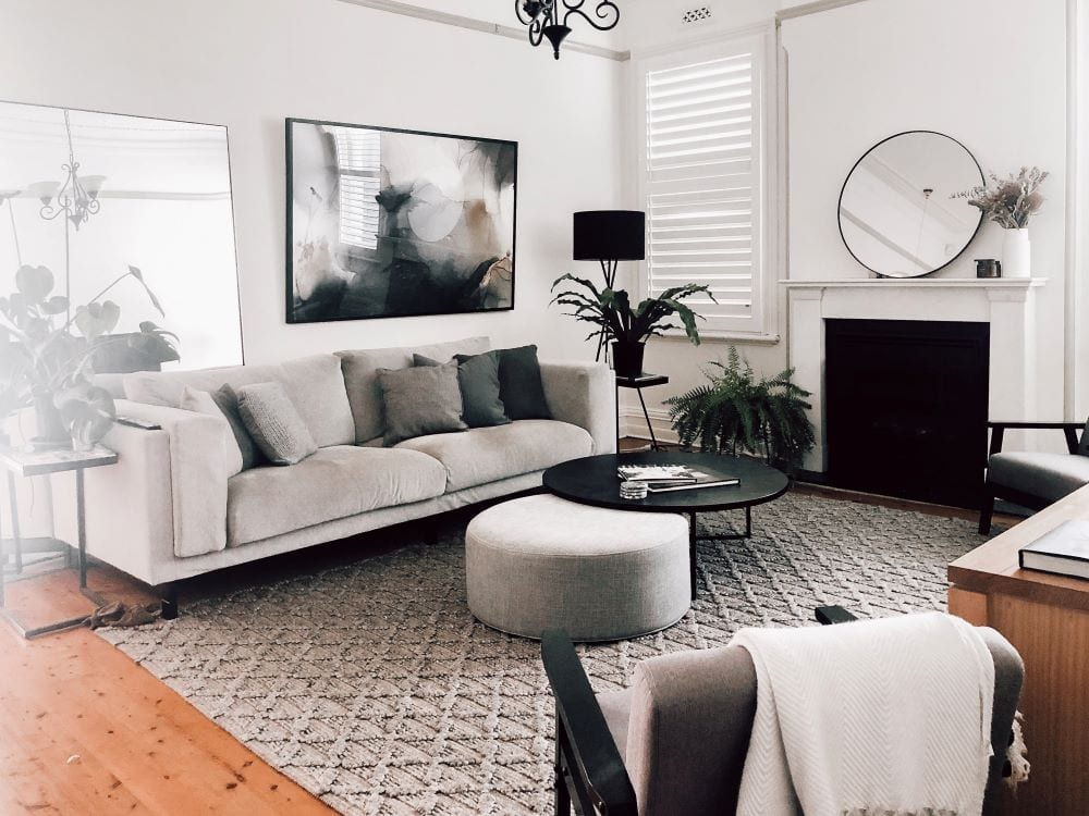 Modern black and white living room, art and mirror mounted on walls