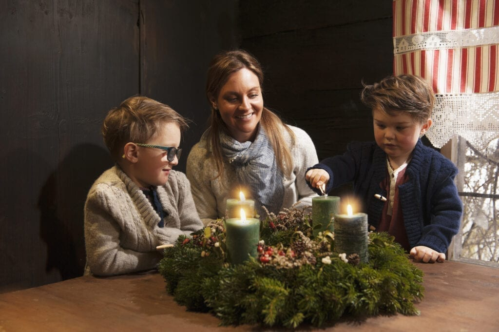 Mother and her two little sons lightning candles on a Advent wreath