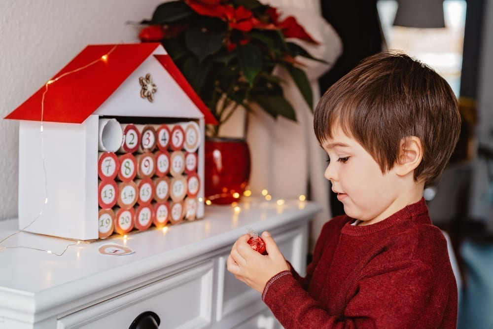 Child opening the first day of an Advent calendar