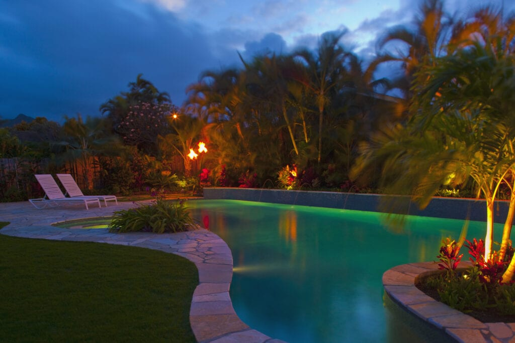 Tropical backyard pool with green lights