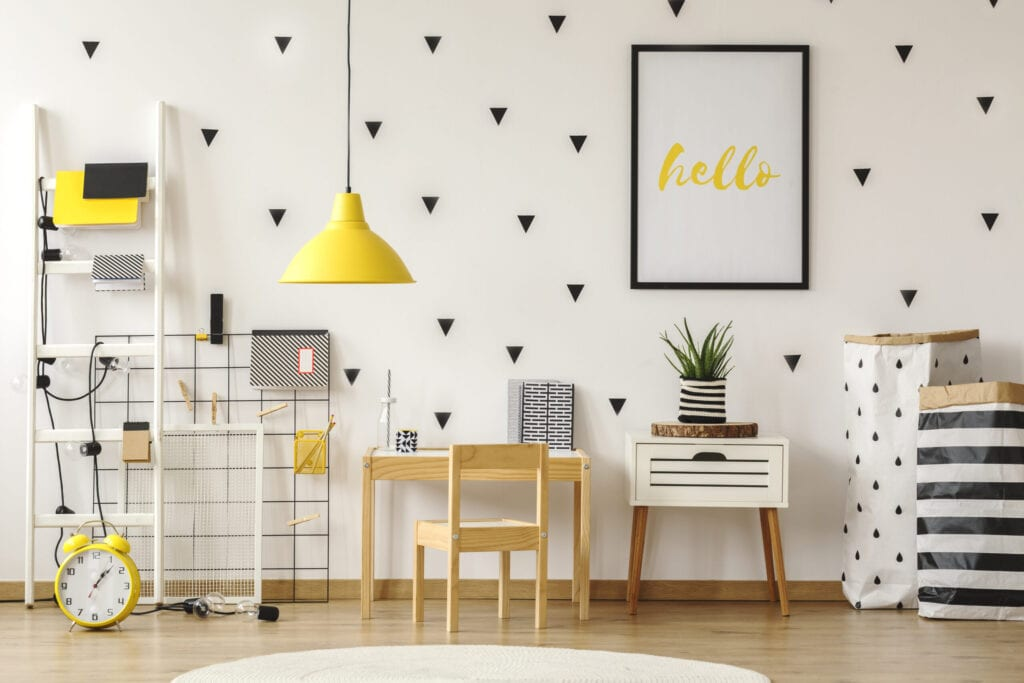 Poster in a black frame on a white wall with stickers in a scandinavian style child bedroom interior with wooden furniture and yellow decorations