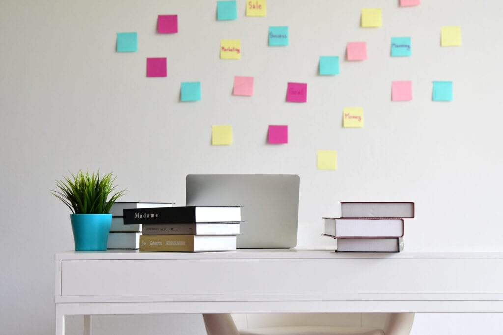 Modern Desk office with books stacked and computer laptop isolated over white wall background at home