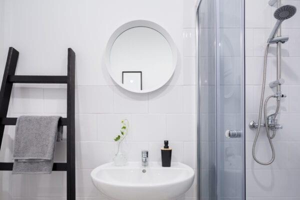 Scandinavian white bathroom with creative ladder shelf for towels
