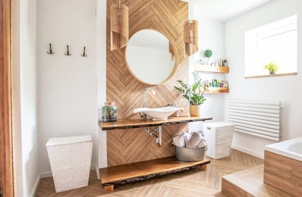 White sink on wood counter with a round mirror hanging above it. Bathroom interior.