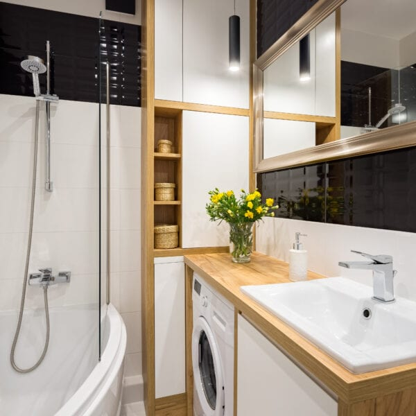 Black and white bathroom with shower and wooden cabinet