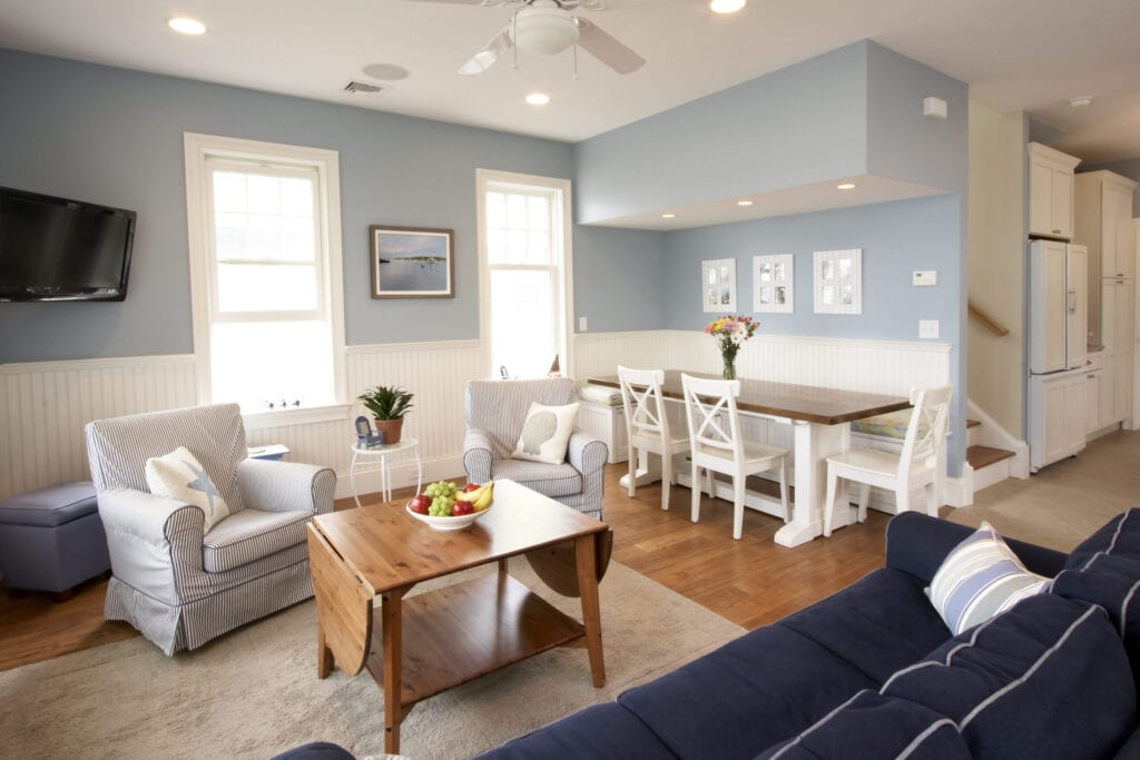 An open floor plan interior of a beach house. Living room and kitchen nook both leading into a galley kitchen and the stairwell bringing you to the three bedrooms.