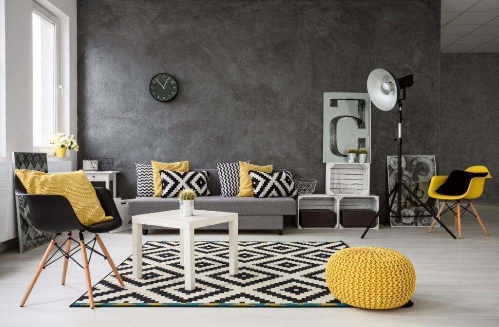 Black and white living room with yellow accents in the pillows and chair