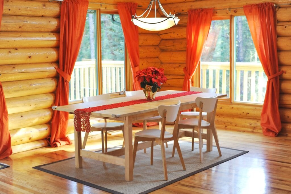 Dining room with hardwood floor in a Candian rustic log house.Outside a wrap-around deck,Canada.
