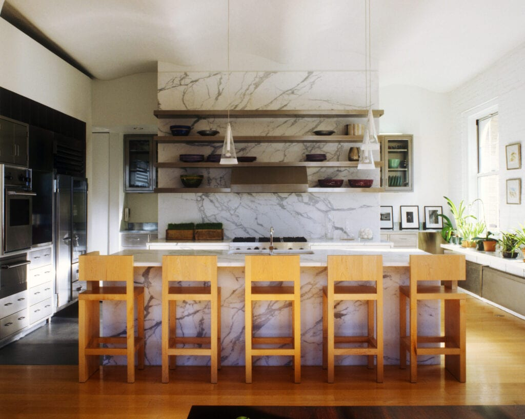 Marble countertops and facings in a kitchen with a Viking range and Spencer Fung stools in this converted Tribeca loft designed by Richard Gluckman.