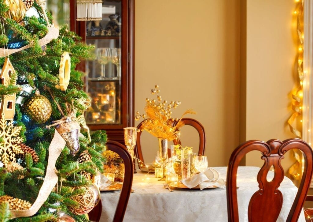 Christmas tree next to dining table with mustard yellow accents