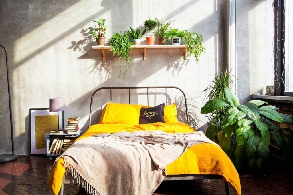 Modern industrial bedroom with yellow quilt on bed