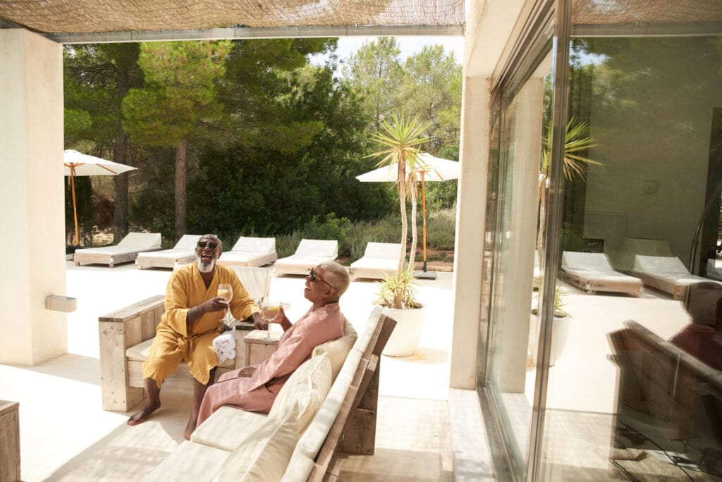 An older couple toast and share a drink on a poolside terrace