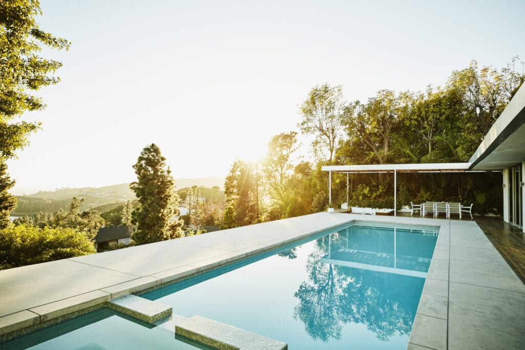 Pool in backyard of modern house at sunset