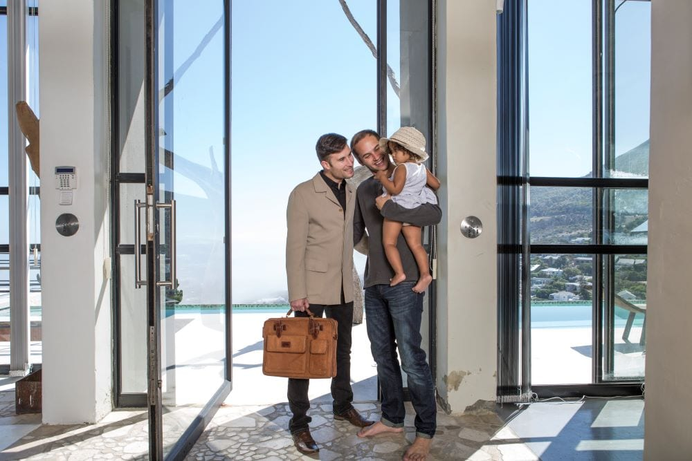 Couple holding baby in front of open glass pivot door