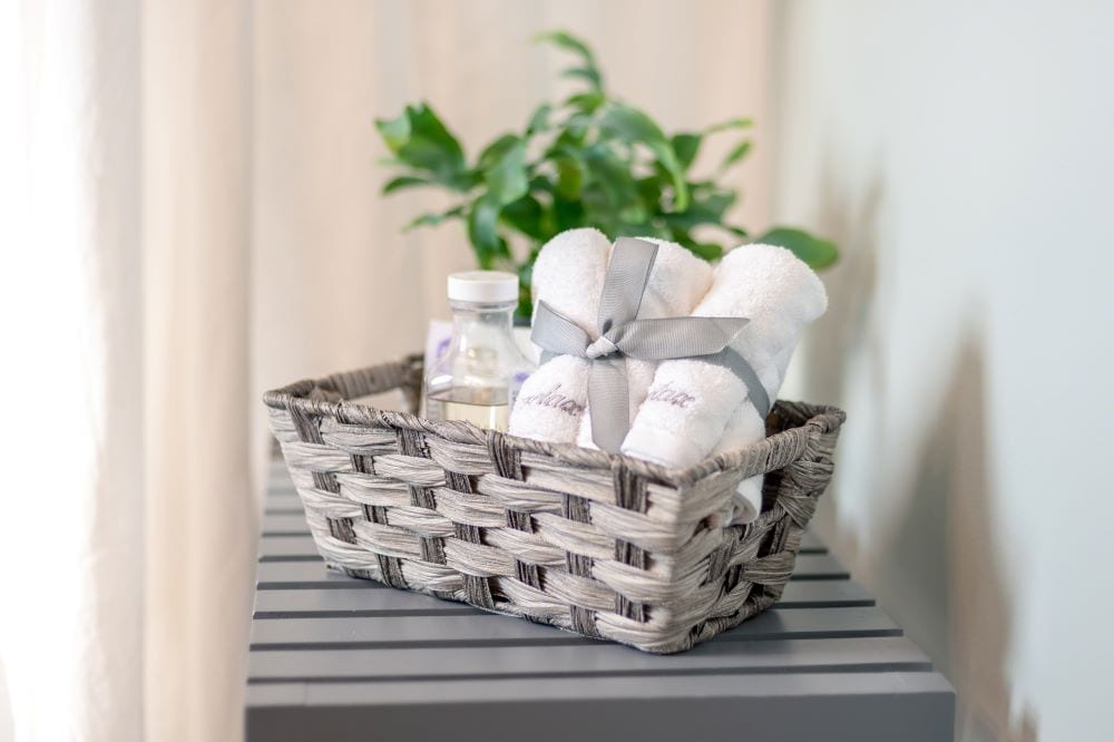Basket holding small hand towels and lotion