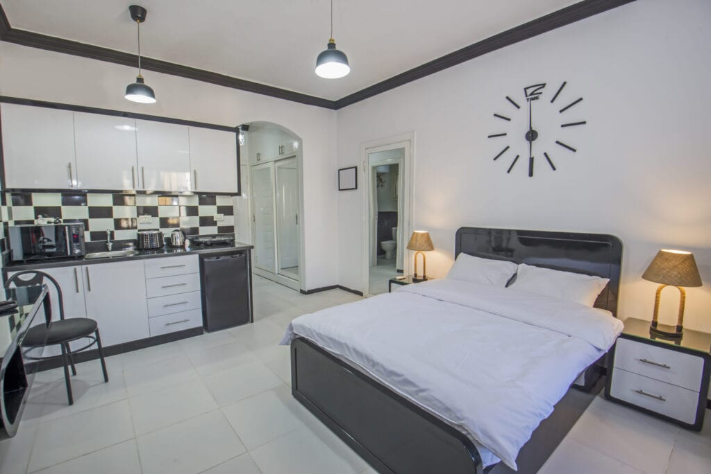 Interior design decor furnishing of luxury studio apartment bedroom with double bed and kitchen area