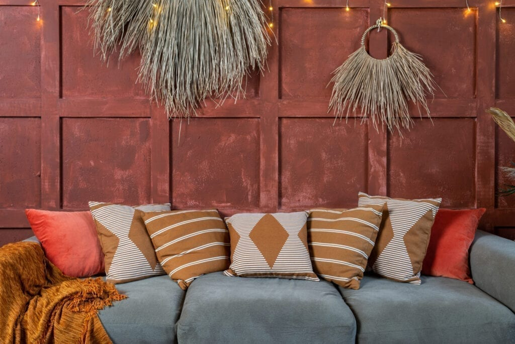 Elements of cozy room with boho style interior, couch or sofa and pillows, cushions near decoration plant composition on orange wall