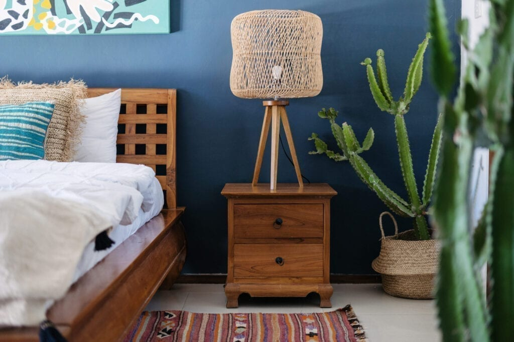 Vertical photo of lamp on wooden bedside table, ethnic decor, comfortable bed, woven ornament carpet and exotical cactus plant in basket. Concept of elegant bedroom interior in cozy house