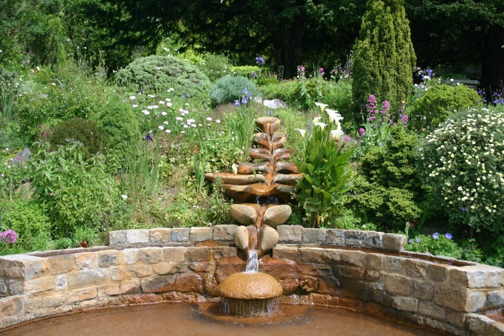 Garden waterfall created from brick and rocks, surrounded by lush green landscaping