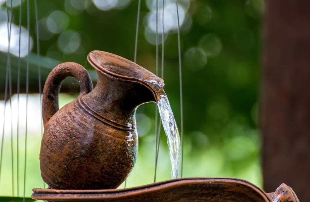 Copper clay water jug creating waterfall in garden