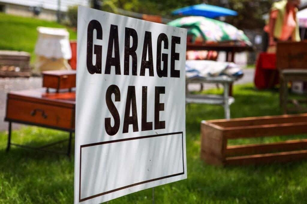 Garage sale sign on grass lawn