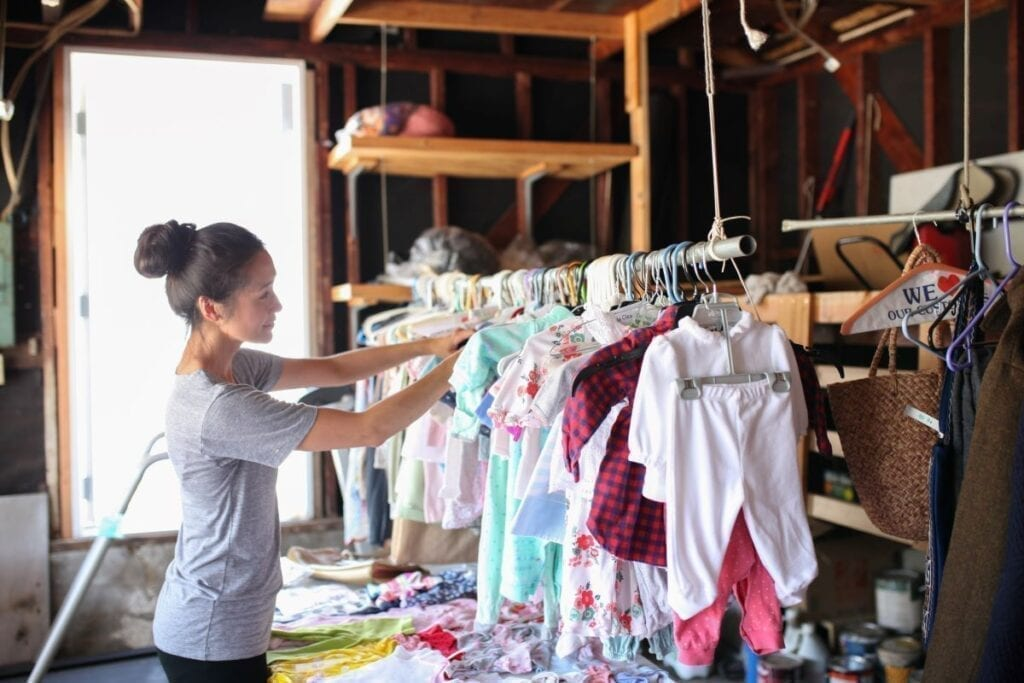 Woman looking through baby clothes at a garage sale