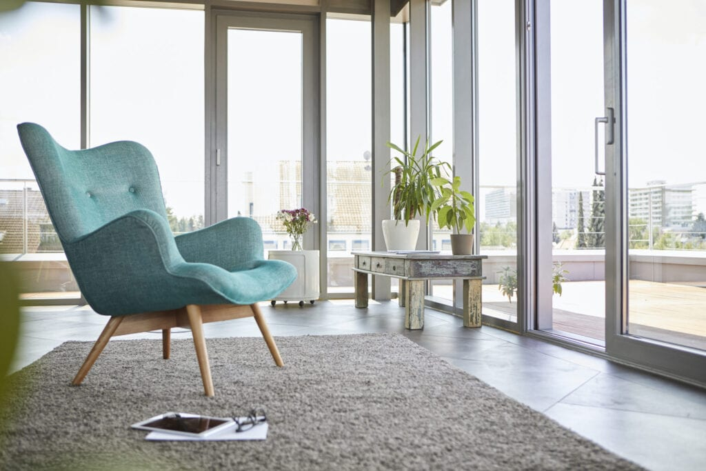 Home interior with armchair, tablet and view on roof terrace