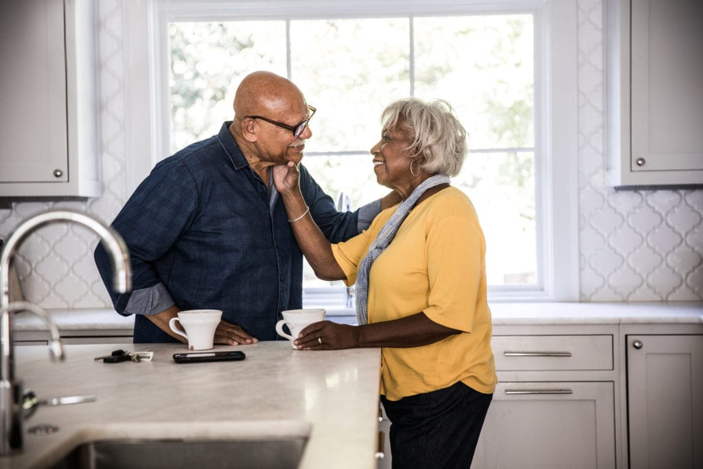 Older couple enjoys coffee in their kitchen.