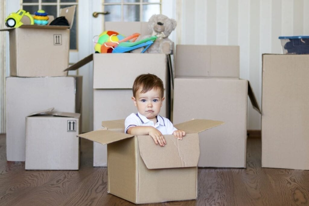 House with stacks of moving boxes, cute kid sitting in cardboard box