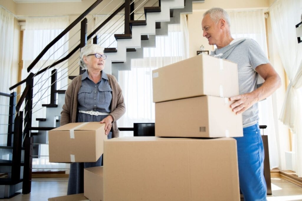 Elderly couple packing boxes, downsizing to smaller home