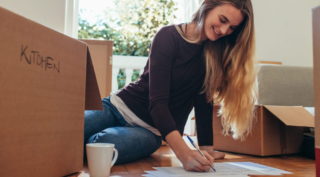 Happy woman sitting on floor making a moving checklist for her new home. Woman making a checklist of household items sitting on floor with packing boxes around her.